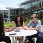 Three students sitting at outdoor table